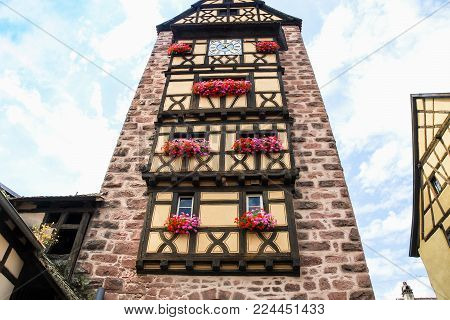 travel to France - facade of old clock tower Riquewihr town in Alsace Wine Route