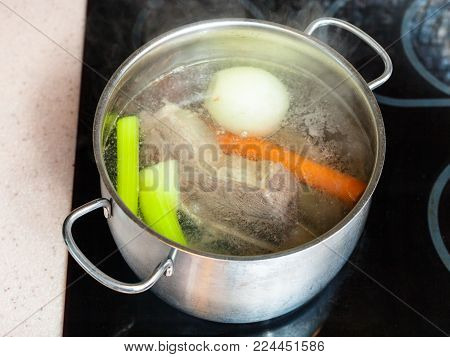 cooking soup - simmering beef broth in stockpot on ceramic cooker