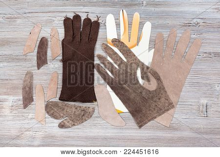workshop on sewing gloves - top view of set of details for glove production on wooden background