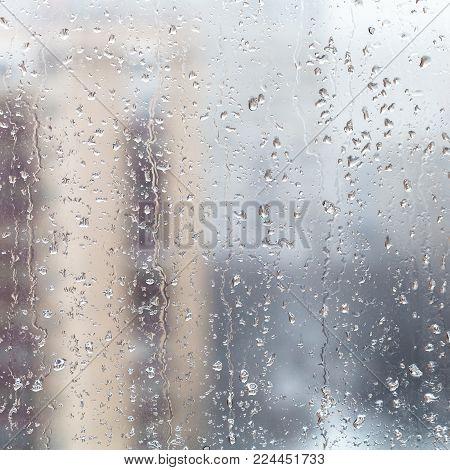 urban background - raindrops on home window glass (focus on water trickles on windowpane) in winter season