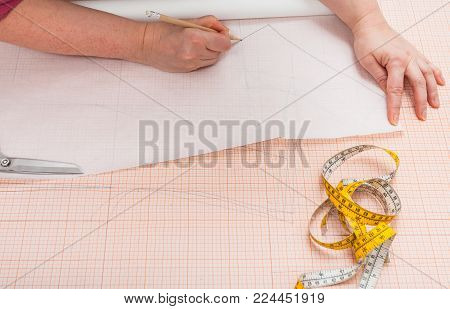 tailor traces the hand drawn clothing pattern on tracing paper