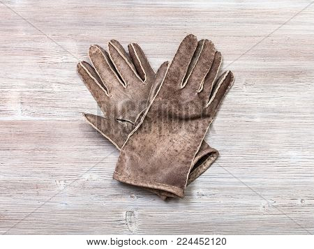workshop on sewing gloves - top view of new hand-made leather gloves on wooden background