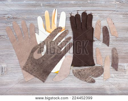 workshop on sewing gloves - top view of set of items for glove production on wooden background