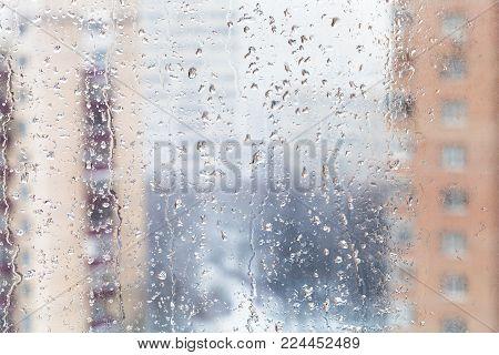 urban background - rain drops on home window glass (focus on water trickles on windowpane) in winter season