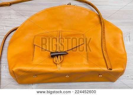 handmade yellow leather bag with pocket on wooden table