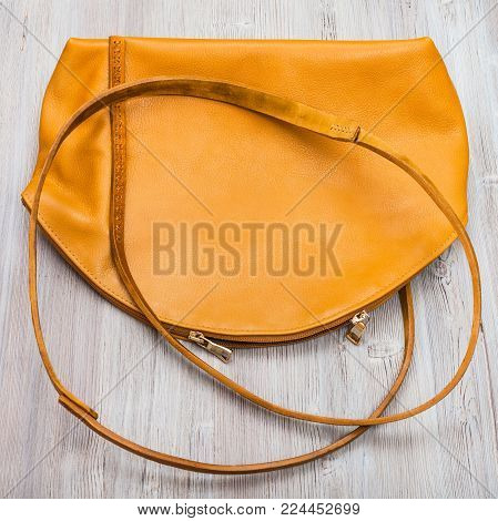 top view of back side of handmade yellow leather bag on wooden table
