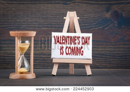 Valentine's Day is coming. Sandglass, hourglass or egg timer on wooden table showing the last second or last minute or time out