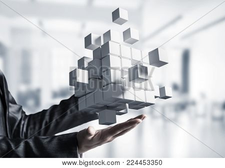 Cropped image of business woman in suit holding multiple white cubes in hands with office view background. Mixed media.