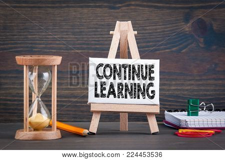 Continue learning. Sandglass, hourglass or egg timer on wooden table showing the last second or last minute or time out