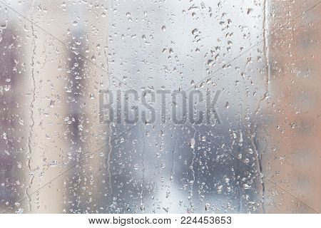 urban background - rain drops on window glass (focus on water trickles on windowpane) in winter day