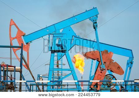 Oil field. The oil pumping unit close up with a torch on a background.