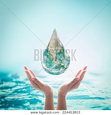 World ocean day, saving water, environmental protection, sustainable ecological ecosystems concept with green earth drop on woman's hands on sea background: Element of this image furnished by NASA