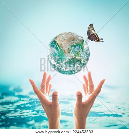 World ocean day, saving water campaign, sustainable ecological ecosystems concept with green earth on woman's hands on blue sea background : Element of this image furnished by NASA