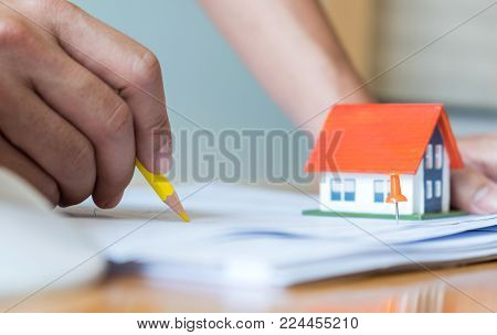 Home Design,Close-up architects are designing the house,model house place on house plan on the desk.