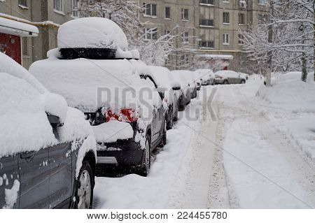 The car, covered with snow. Heavy snowfall, precipitation. The problem of motorists