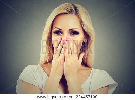 Closeup portrait of a happy woman being shy laughing and covering face with hands