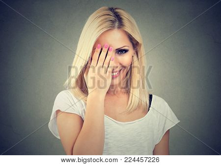 Portrait of a beautiful woman with long blonde hair wearing white t-shirt, looking shy with hand on face and smiling, on gray wall background
