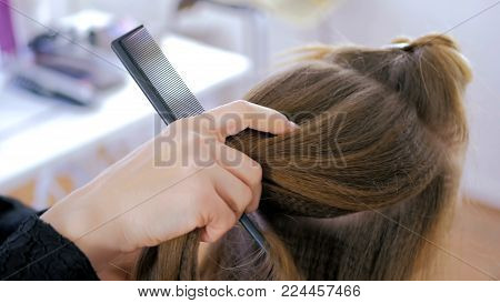 Professional hairdresser, stylist doing hairstyle for young pretty woman with long hair and using barrette for fixing hairdo in white make up room. Beauty and haircare concept