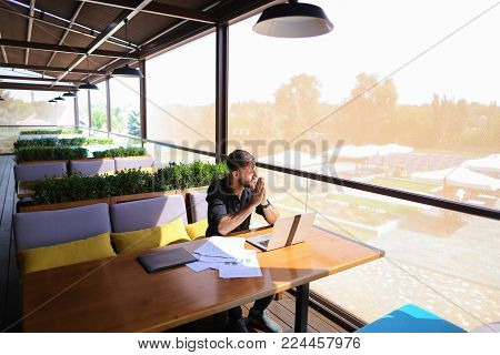 Copywriter typing article from papers on laptop keyboard and hurrying. Hardworking dressed in black shirt looks tired. Concept of website content writers and creating text for advertising.