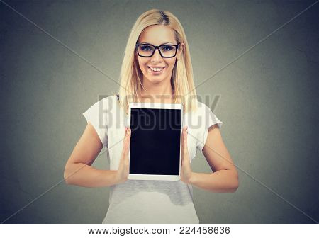 Casual young woman in eyeglasses demonstrating new tablet showing screen at camera.
