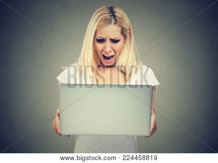 Shocked woman looking at laptop computer anxious with open mouth. Human emotion reaction
