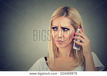 Angry woman talking on her cell phone on a gray background