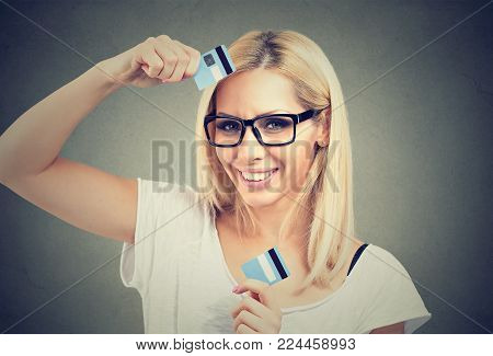 Young delightful woman in glasses holding cut halves of credit card smiling at camera.