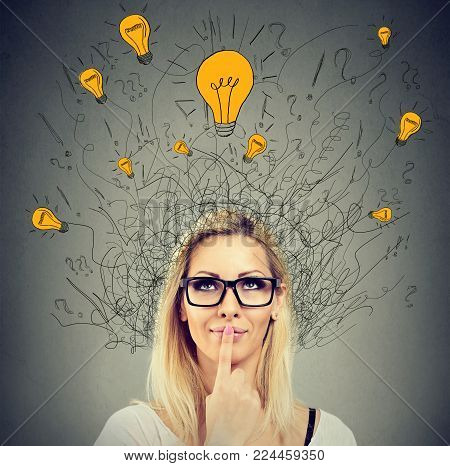 Brain connections. Happy thoughtful woman looking up at many ideas light bulbs above head isolated on gray wall background. Eureka concept