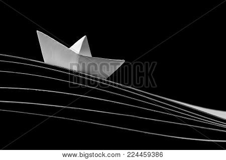 One white paper boat in the dynamics on the waves and on a black background.