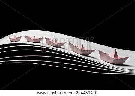 a team of five pink paper boats in the dynamics on the waves and on a black background. 5 pink ships of different sizes
