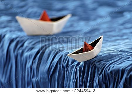 paper boats in the dynamics on the waves and on a blue wave. ships on waterfall