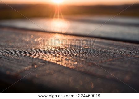 Wood table top against the sunlight with lensflare and golden glow. For product placement or advertisement