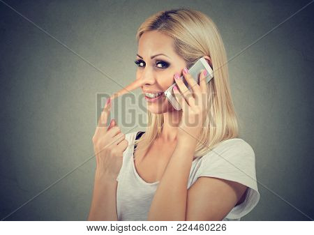 Happy young liar woman with long nose talking on mobile phone isolated on gray wall background. Human emotion