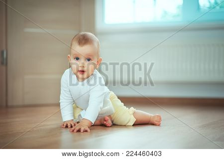 Adorable little baby sitting in bedroom on the floor with bottle with milk or water and laughing. Infant Childhood Kids People concepts. Cozy home with children Lifestyle