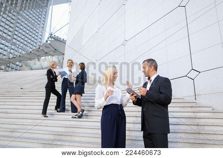 Financial team members going down stairs with tablet, document case and talking by smartphone in  . Concept business partners leaving conference with positive emotions. Successful young people wear suits and shirts.