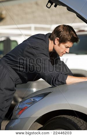 Young mechanic fixing a car
