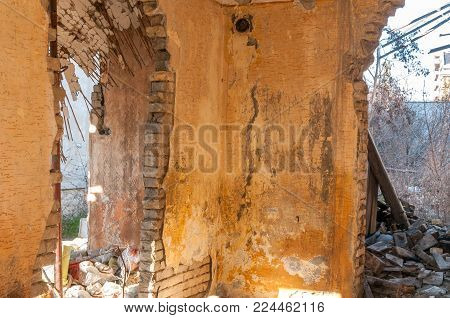 Interior remains of hurricane or earthquake disaster damage on ruined old house in the city with collapsed walls and bricks