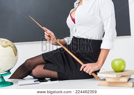 cropped shot of sexy teacher with pointer sitting on desk