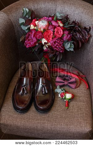 Set of trendy mens clothes and accessories in red colors. Groom red dotted bow tie, lacquered brown shoes, wedding trendy bouquet and boutonniere on the chair