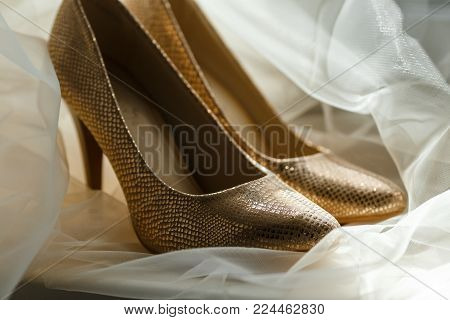 Beige bridal shoes standing on the floor, covered with a white veil