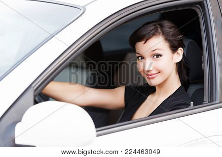Pretty woman driver smiling to you from the white car