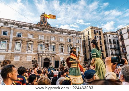 Barcelona, Spain - May 29, 2016: Giant puppets Gigantes of the Corpus Christi festival move among viewers in front of the historical town hall with spanish and catalan flags.
