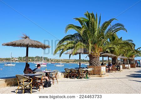 ALVOR, PORTUGAL - JUNE 7, 2017 - Tourists relaxing at a pavement cafe along the promenade with views of yachts moored in the estuary, Alvor, Algarve, Portugal, Europe, June 7, 2017.