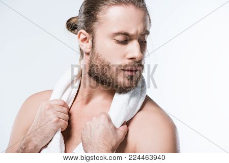 Caucasian man holding white bath towel around his neck and looking away, isolated on white