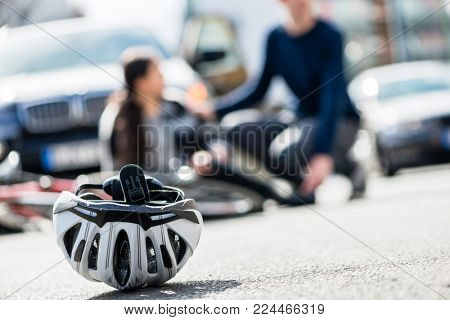 Close-up of a bicycling helmet fallen down on the ground after accidental collision between bicycle and a 4x4 car