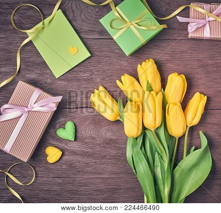 Mothers Day background. Tulips Bouquet, Gift boxes on wood. Beautiful Spring yellow tulips, presents. Creative Romantic Style. Colorful holiday, tulips. Vintage