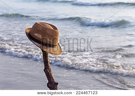View of the sandy beach with a brown hat on the beach near the sea. The swash of seawater up the beach after the breaking of a wave. Background with copy space and visible sand texture.