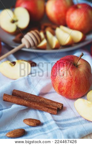 Country still life with apples. Whole and sliced apples with honey, cinnamon and almond nuts on white checked kitchen towel. Cosy village food photo concept.