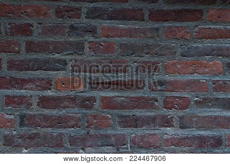 Weathered texture of grey and red aged brick wall background. Smooth and blurry texture with scrapes and marks of the past times