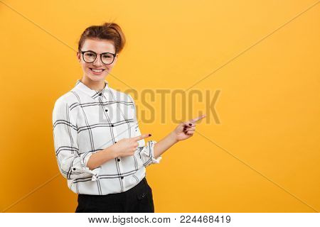Portrait of attractive woman in eyeglasses pointing two fingers aside at copy space isolated over yellow background